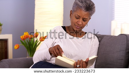 Mature African woman reading book on couch