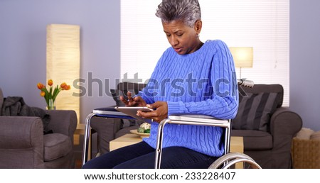 Mature African woman sitting in wheelchair with tablet