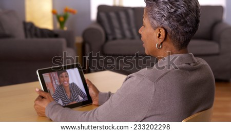 Mature African woman talking with granddaughter on tablet - stock photo