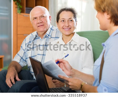 Mature american couple filling questionnaire for employee with laptop of the bank