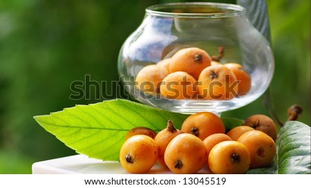 Mature and flavorful Loquats with in a glass container. - stock photo