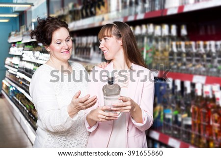 Mature and young women selecting bottle of vodka in shop