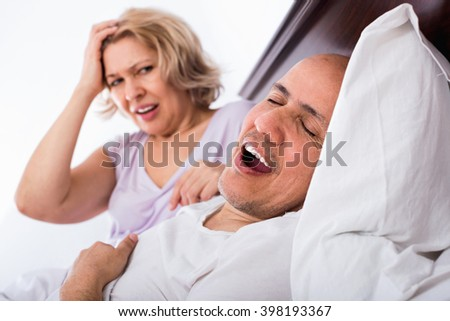 Mature  angry girlfriend cannot stand guy snoring loudly in sleep
