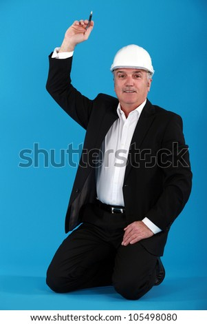 Mature architect kneeling on the floor with arm raised - stock photo