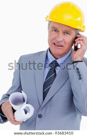 Mature architect talking on his cellphone against a white background