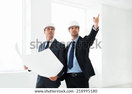 Mature architects in helmets indoor