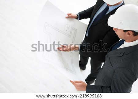 Mature architects with plan