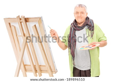 Mature artist drawing on an easel isolated on white background - stock photo