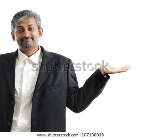 Mature Asian Indian businessman arm out showing empty space, isolated on white - stock photo