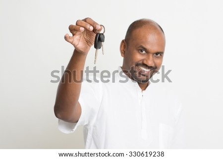 Mature Asian Indian estate agent or salesman showing a key, India male business man, standing on plain background with shadow.