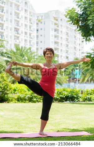 Mature Asian woman doing stretching exercise for her legs in the park - stock photo