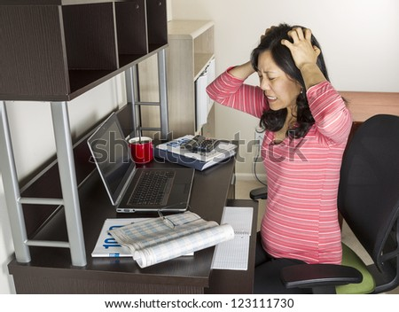 Mature Asian woman express frustration while doing income taxes with tax form booklet, calculator, coffee cup, glasses and computer on desk - stock photo
