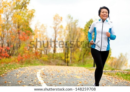 Mature Asian woman running active in her 50s. Middle aged female jogging outdoor living healthy lifestyle in beautiful autumn city park in colorful fall foliage. Asian Chinese adult in her fifties. - stock photo