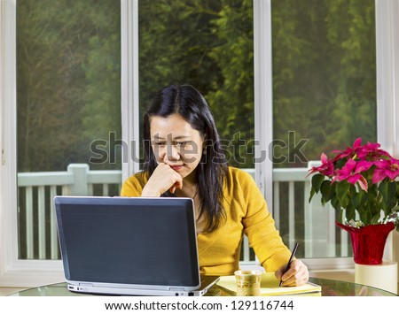 Mature Asian woman working at home with notebook computer on glass table with large windows in background - stock photo