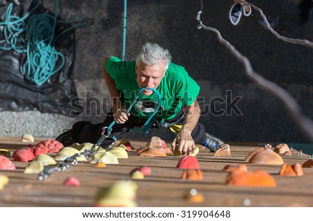 Mature Athlete Fixing Rope into Belaying Device Aged Male Climber Moving Up on Outdoor Climbing Wall on Veterans Extreme Sport Competitions - stock photo