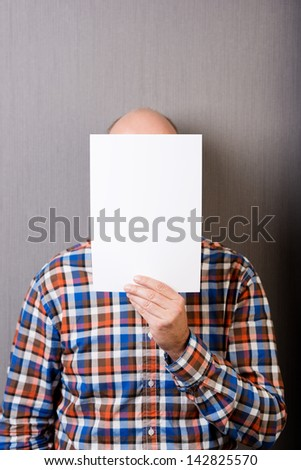 Mature balding man holding a blank white paper sheet with copy-space, in front of face, with a gray wall as background - stock photo