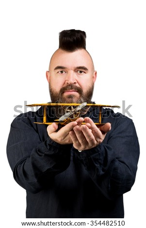 Mature bearded man holding a toy airplane in hands, isolated