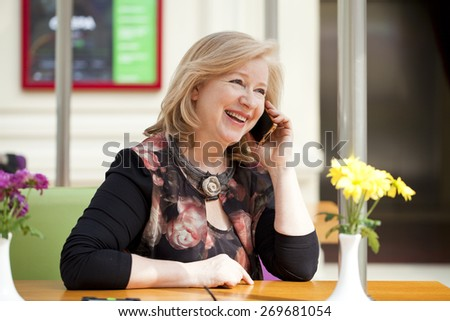 Mature beautiful blonde woman is calling on a cell phone while sitting in a coffee shop - stock photo