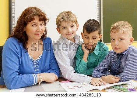 Mature beautiful woman teacher reads with three primary school pupils a book at the table. Multi-ethnic group. Horizontal color image. - stock photo