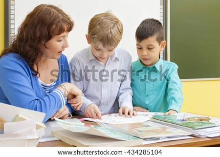 Mature beautiful woman teacher reads with two primary school pupils a book at the table. Multi-ethnic group. Horizontal color image. - stock photo