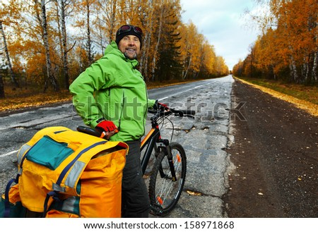 Mature bicycle tourist with his loaded bike on an asphalt autumn road - stock photo