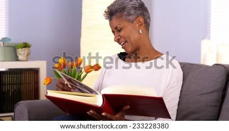 Mature Black woman looking through photo album - stock photo