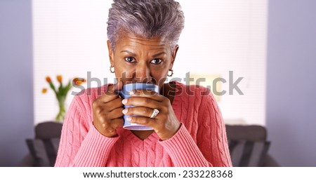 Mature black woman smiling with coffee mug - stock photo