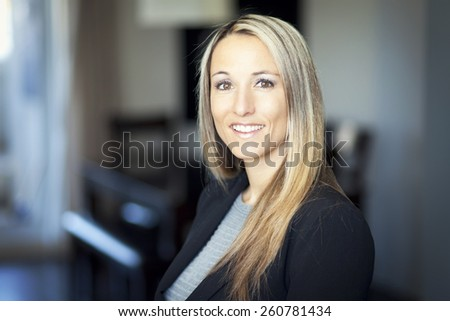 Mature blond woman smiling at the camera - stock photo