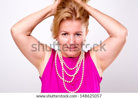 Mature blonde lady with both arms up holding her hair, she has pearl necklace and  pink shirt