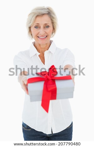 Mature blonde smiling at camera holding gift on white background - stock photo
