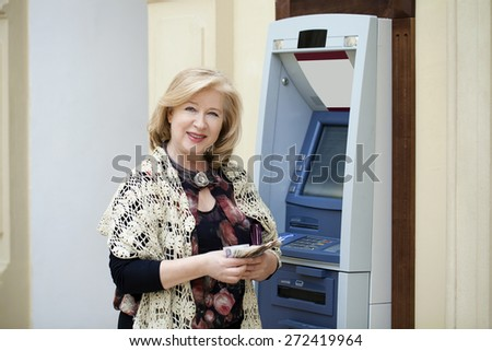 Mature blonde woman counting money near automated teller machine in shop - stock photo