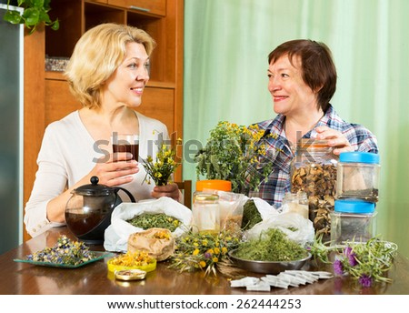 Mature blonde woman drinking herbal tea with her neighbor