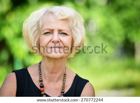 Mature, blonde woman in garden, - stock photo