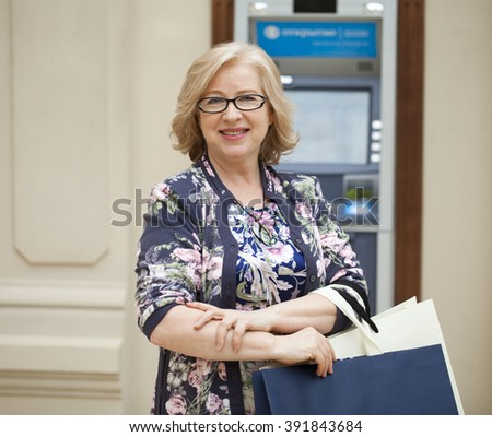 Mature blonde woman with shopping bags on the background of the ATM - stock photo