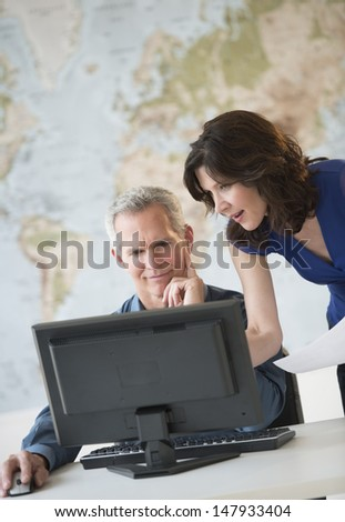 Mature business colleagues working at office desk with world map in background - stock photo