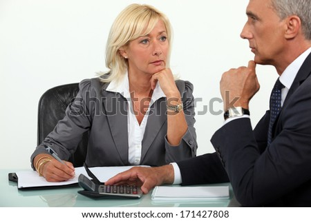 Mature business couple at a desk - stock photo
