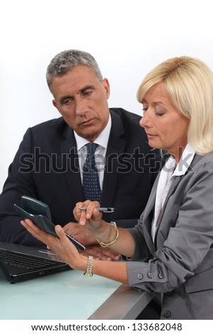 Mature business couple with a  calculator - stock photo