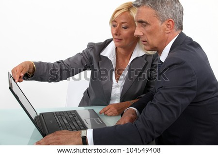 Mature business couple with a laptop - stock photo