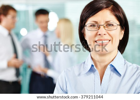Mature business leader looking at camera with colleagues communicating on background