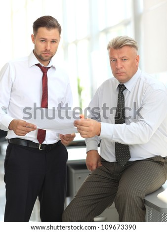 Mature business man discussing with his colleague while at work