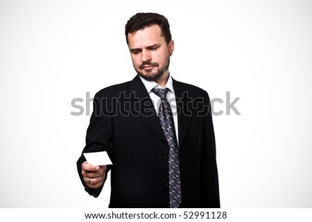 Mature business man looking at a blank business card over white background - stock photo