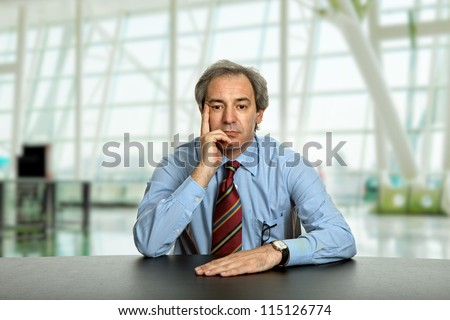 mature business man on a desk at the office - stock photo