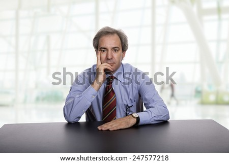 mature business man on a desk, at the office - stock photo