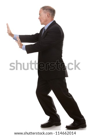 mature business man pushing invisible object on white - stock photo
