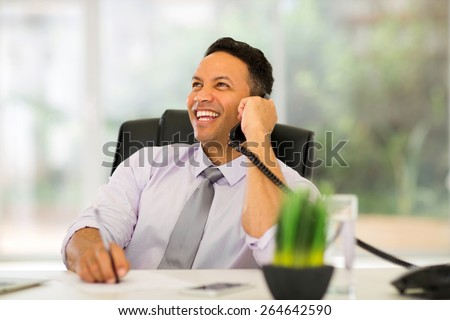 mature business man talking on landline phone in modern office - stock photo