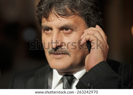 Mature business man talking with a mobile phone - stock photo