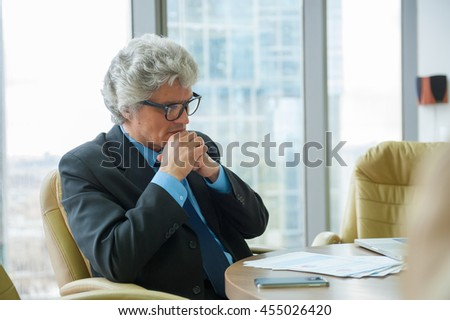 Mature business man works with docs in modern office - stock photo