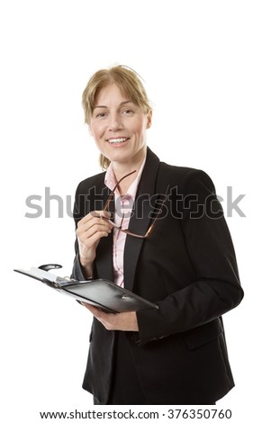 Mature business model is looking in her diary whilst holding her glasses in her right hand.  Isolated on white.