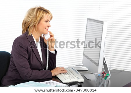 Mature business woman calling by phone in the office. - stock photo