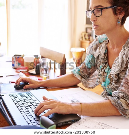 Mature business woman frustrated by her outdated laptop computer while working at her desk in her home office - stock photo